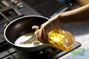Someone pours cooking oil into a pan