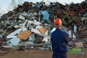 Worker stands in front of pile of recyclable materials